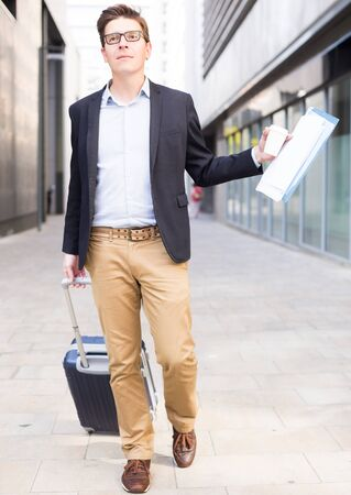 cheerful worker in suit standing with baggage and documents at the city