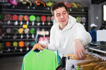interested tennis male is choosing new shirt for play in time shopping in the sports store