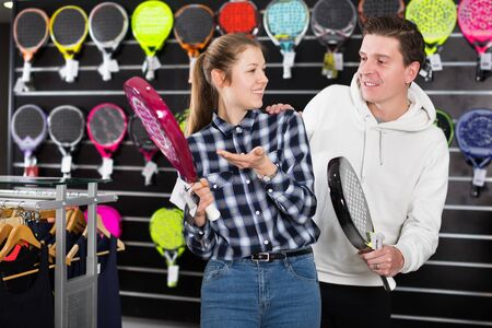 Young female with male are standing in sportwear with new racket and balls for padel in a speciality store. Focus on both persons Imagens