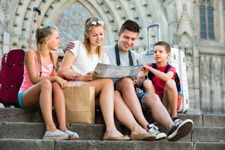 Cheerful  family of four relaxing on old cathedral steps looking map 写真素材