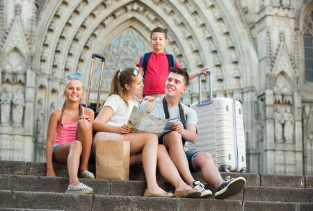 Portrait of happy family of four sitting on stone stairs near cathedral, using map 写真素材