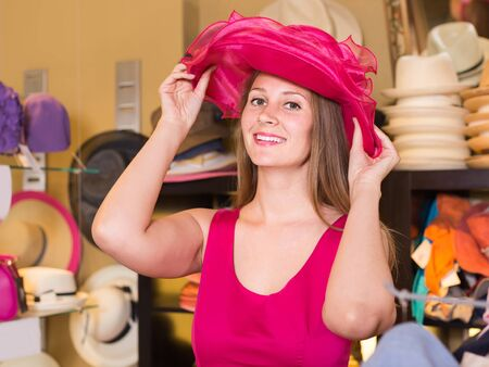adult positive russian girl try on pink headwear in store