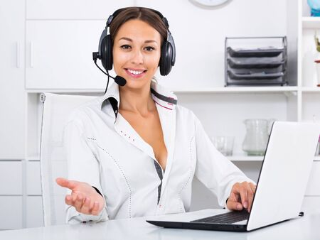 Happy woman talking with customer using hands-free set at call center Reklamní fotografie