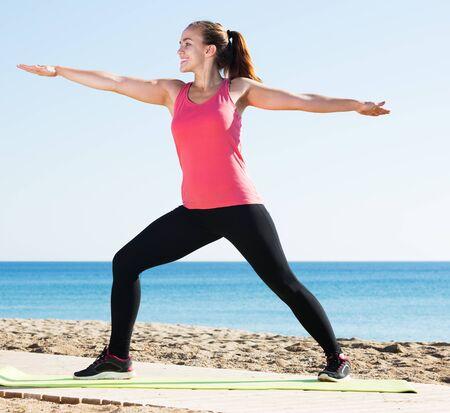 Junge kaukasische Frau, die an einem sonnigen Tag Yoga am Meer macht Standard-Bild