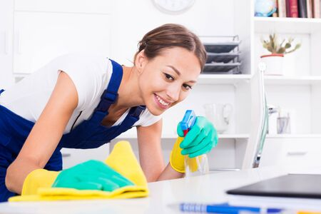 smiling woman in protective coveralls cleaning at office