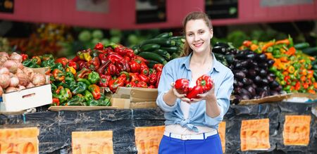 Portrait of happy  woman who is choosing pepper in the market.