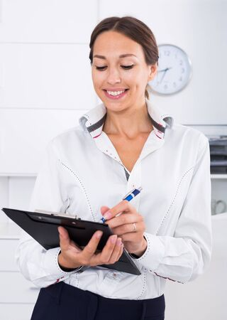 smiling business female employee holding clipboard in hands in firm office Stock Photo
