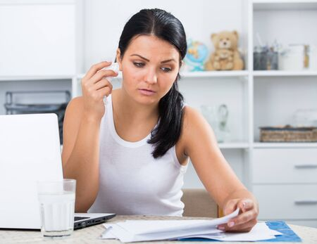 Young brunette sad woman working at laptop