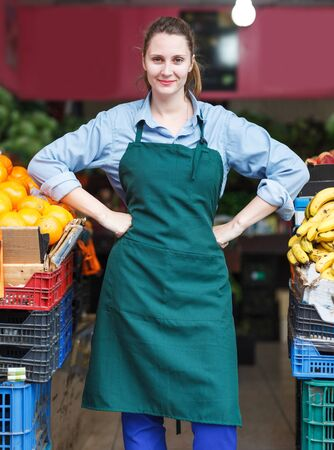 Portrait of woman seller who is standing on her workplace in the market. Stock Photo