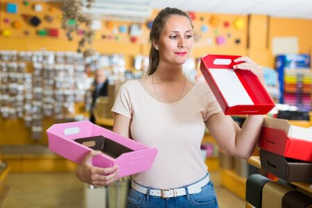 Woman is choosing red or pink palettes for trifle in store.
