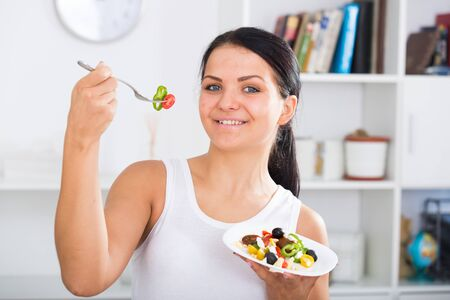 Young woman holding fork and plate of salad