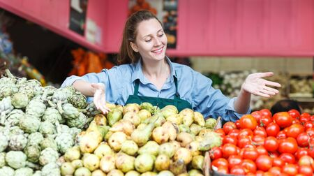 Portrait of smiling woman seller who is standing on her workplace in the market. Stock Photo