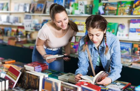 Smiling young woman with girl picking textbooks for school in book store Stok Fotoğraf