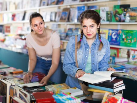 smiling glad woman showing open book to girl in school age in book boutique