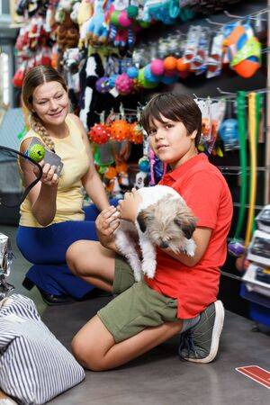 Cheerful customers choosing necessary accessories for their dog in pet store