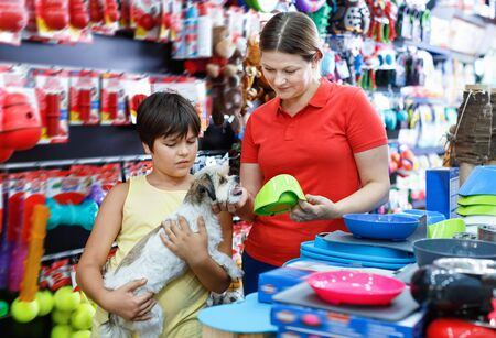 Happy glad  teen boy with mother visiting pet shop in search of accessories for their dog