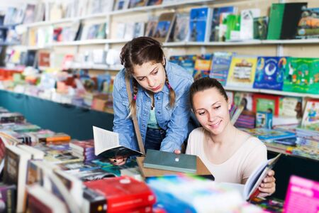 Portrait of smiling woman with teen girl picking textbooks for school in book store Reklamní fotografie