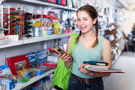 Cheerful teenager buying different products in stationery shop Reklamní fotografie