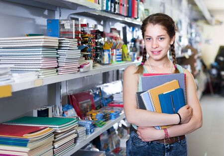 Energetic young girl buying different products in stationery shop