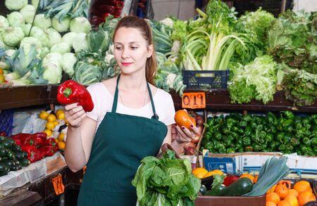 Friendly seller woman is demonstraiting pepper in the market.