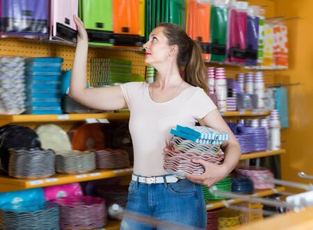 Cheerful girl with disposable tableware in her hands chooses disposable tableware in store Stockfoto
