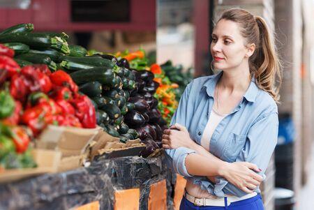 Portrait of positive woman who is choosing aubergine in the market Reklamní fotografie