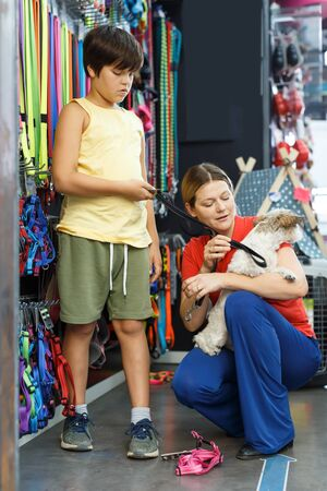 Laughing family choosing necessary accessories for their dog in pet store Reklamní fotografie