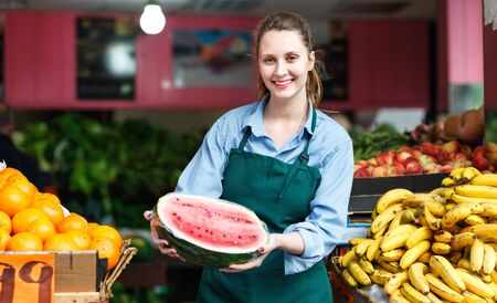 Glad pleasant smiling seller woman is standing with watermelon on her workplace in the market. Reklamní fotografie