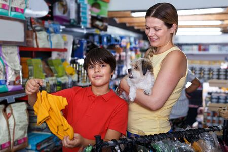 Careful preteen boy with mother visiting pet shop in search of clothes for their havanese puppy
