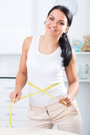 Brunette smiling with measuring tape on waist