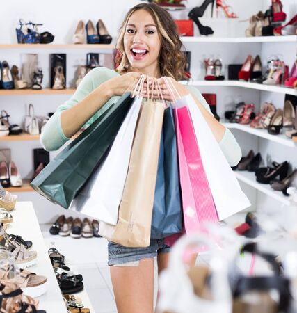 Happy young girl is showing bags with purchases in store