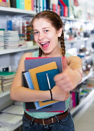 Cheerful young girl buying different products in stationery shop Reklamní fotografie