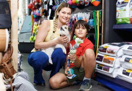 Cheerful Smiling female with preteen boy and small dog looking pet supplies in pet shop