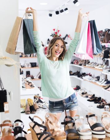 Positive girl is showing purchases in shoes shop