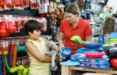 Cheerful woman with preteen son and little dog buying pet supplies in store