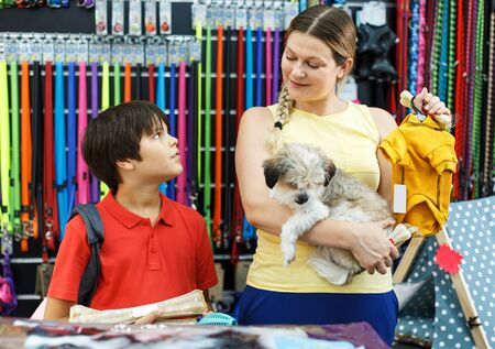 Careful preteen boy with mother visiting pet shop in search of clothes for their dog Reklamní fotografie