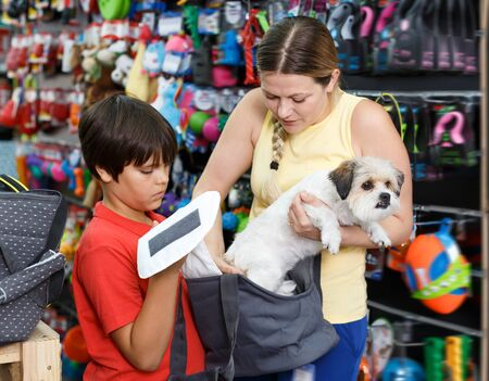 Jolly  teen boy with mother choosing bag dog carrier for their puppy in pet supplies store