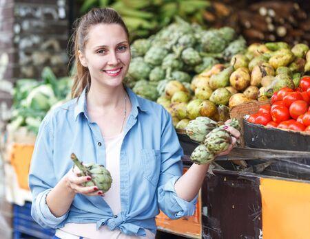 Portrait of positive woman who is choosing artichokes in the market Imagens