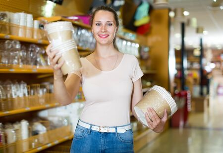 Glad girl with disposable tableware in her hands chooses disposable tableware in store