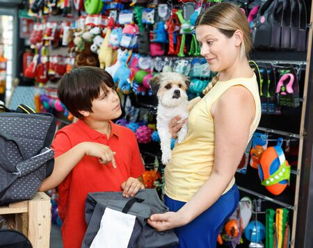 Careful cheerful positive smiling family visiting pet shop in search of bag for transportation for their dog