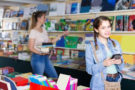 Female teenager is choosing book while chatting in bookstore. Reklamní fotografie