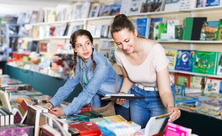 woman showing open book to girl in school age in book boutique