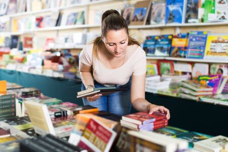 Portrait of smiling young woman buying textbooks in book shop