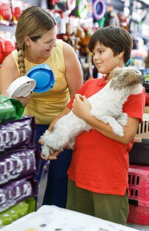 Joyful family choosing necessary accessories for their dog in pet store Reklamní fotografie