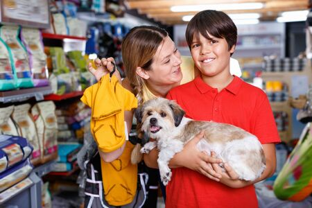 Teen glad positive  boy with mother choosing dog clothes for their puppy in pet supplies store Stockfoto