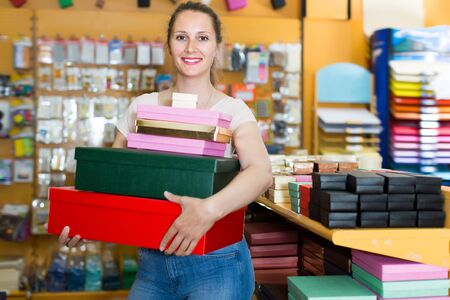 Glad adult girl with gift boxes in her hands in store Stockfoto