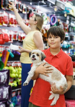 Portrait of cheerful preteen boy with havanese pup while shopping with mother in pet store