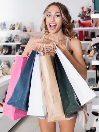 Young female is showing bags with purchases in shop