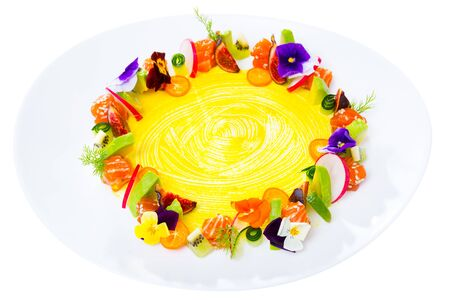Fresh trout tartare formed as wreath with ripe figs, kumquat, kiwi fruit, lime, cucumber, avocado and pansies flowers on plate. Isolated over white background