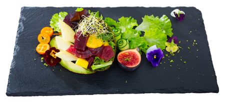Fresh tuna salad with ripe avocado and mango decorated with fruits, greens and pansies flowers served on black board. Isolated over white background